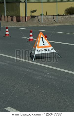 A german folding sign on a road that says sewerage works (Kanalarbeiten)