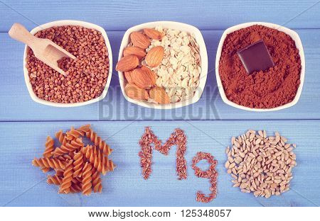 Vintage photo Inscription Mg ingredients and products containing magnesium and dietary fiber healthy nutrition wholemeal pasta sunflower buckwheat oatmeal linseed almonds chocolate powdery cocoa