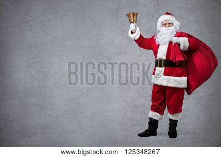 Santa Claus with sack of gifts, ringing in a bell