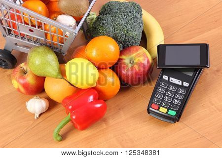 Payment terminal credit card reader with mobile phone with NFC technology and fresh fruits and vegetables with plastic shopping carts cashless paying for shopping