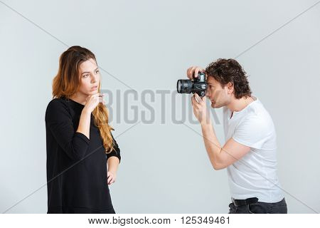 Man photographing female model isolated on a white background