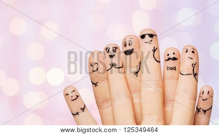 gesture, family, people and body parts concept - close up of two hands showing fingers with smiley faces over pink holidays lights background