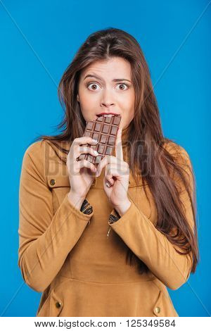 Shocked amazed young woman biting chocolate bar over blue background