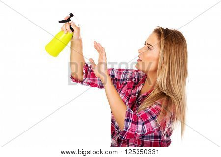 Young woman holding a watering spray bottle