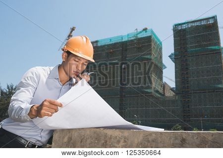 Young Vietnamese engineer looking at blueprint when talking  on walkie-talkie