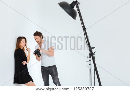 Man photograph and female model looking on camera screen in studio with equipment
