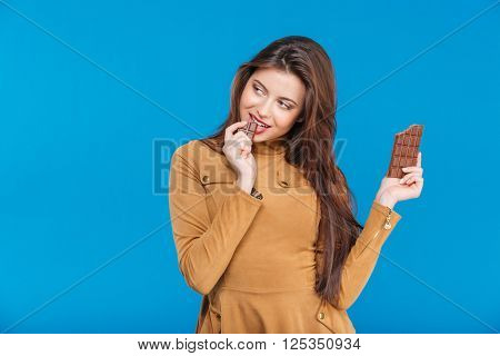 Beautiful playful young woman flirting and eating chocolate over blue background