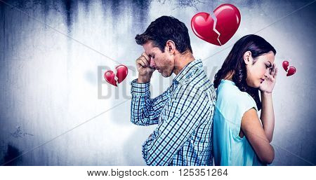 Depressed couple standing back to back against heart