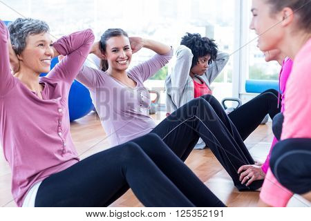 Women exercising on floor with hands behind head in fitness studio