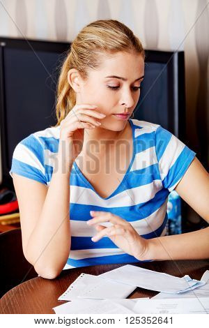 Worried woman sitting at the desk with bills