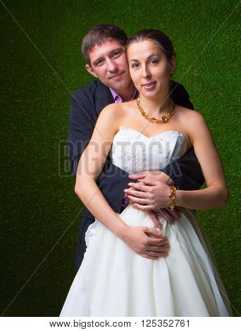 Happy pregnant bride and groom embracing together with stomach unborn child