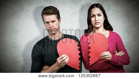Portrait of serious couple holding cracked heart shape against white background