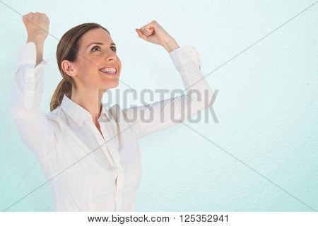 Successful businesswoman with clenched fists looking up against grey wall