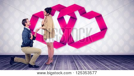 Handsome man proposing woman while kneeling against room with wooden floor
