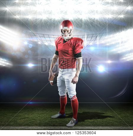 Portrait of american football player holding football against american football arena