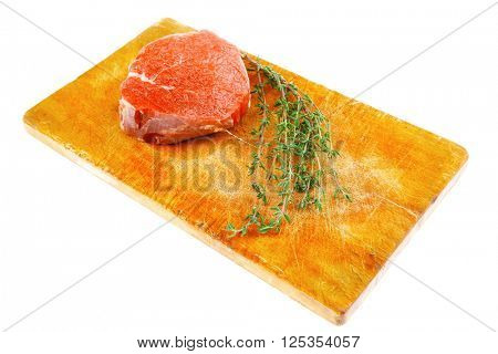 red raw fillet chops : fresh beef meat with thyme on wooden plate . isolated over white background