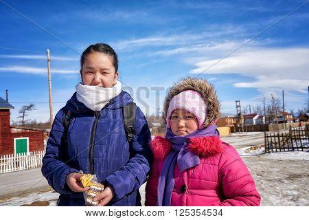 KHANKH MONGOLIA - March 11 2016: Modern Mongolian children . Two little girls go to school in village school