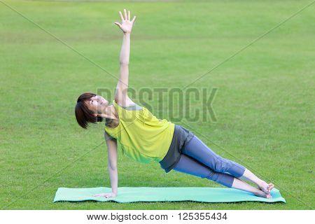 Japanese woman outside doing yoga Side Plank Pose