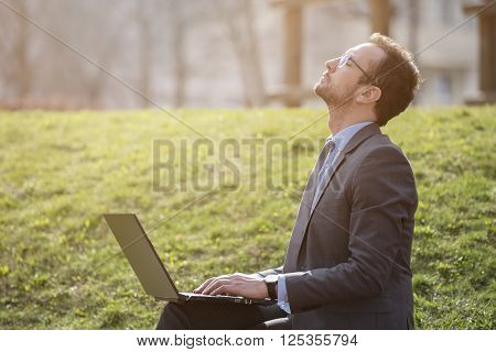 Businessman holding laptop outdoors and filling energy from sunrays