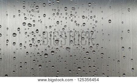 Arranged in 16:9 many small rain drops glowing on a sheet of grey steel.