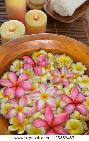 Frangipani in wooden bowl with candle,towel on mat