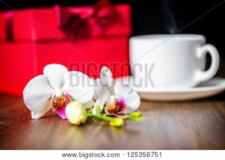Festive Concept Of Mother's Day With Greeting Red Box, Orchid Flower, Phalaenopsis And Cap Of Tea On