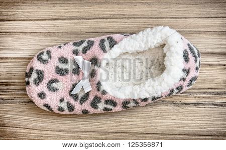 Wool slipper on the wooden background. Beauty and fashion. Retro style.