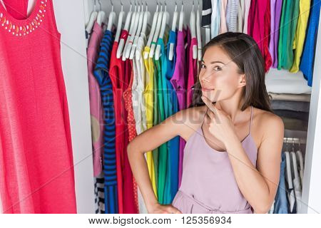 Home closet or store clothing rack changing room. Woman choosing her fashion outfit. Shopping girl thinking what to wear in front of many choices of dresses and clothes in organized clean walk-in.