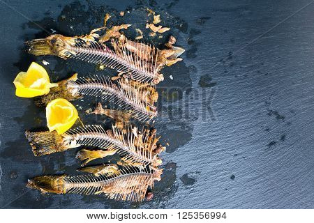 top down of fish skeleton bones without heads squeezed lemon on slate background close up