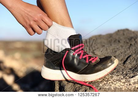 Runner putting on running shoes and fitness socks closeup outdoors on mountain background. Female athlete getting ready for marathon race preparing her feet on trail run.