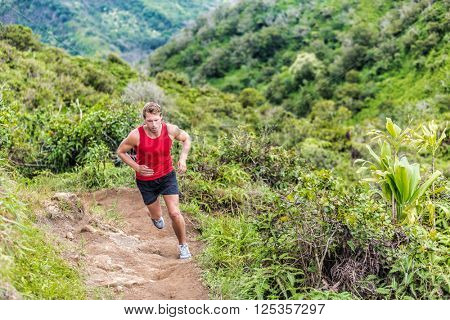 Trail runner running in summer mountain nature landscape on difficult path in mountains in summer wilderness. Athlete jogger working out cardio going up on cross country race uphill outdoors.