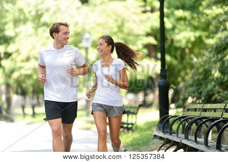 Runners jogging together in New York City Central Park, USA. Healthy couple of new yorkers athletes friends running in summer sun working out a cardio exercise on Manhattan, United Sates of America.