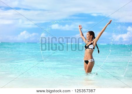Happy bikini woman having fun swimming in ocean. Freedom bikini woman carefree with arms up splashing water in joy on tropical beach. Success Asian girl on summer Caribbean travel vacation.