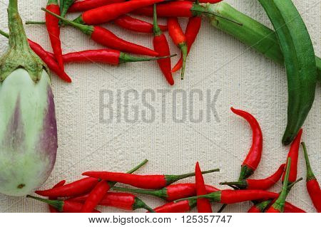 Eggplant or aubergine, chili and ladies' finger arranged carefully and beautifully on textured background. View from above. Flat lay. Background.