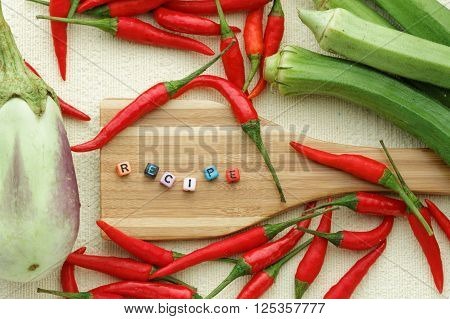 Eggplant or aubergine, chili, ladies' finger and one wooden spatula arranged carefully and beautifully on textured background with alhabet block forming word RECIPE. View from above. Flat lay.