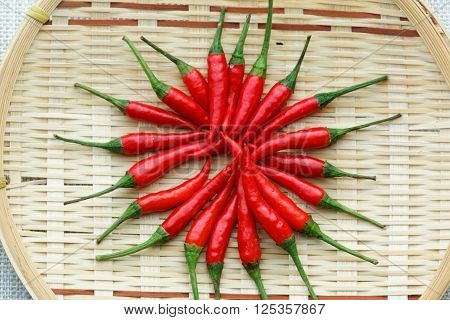 Red chili pepper carefully arranged in a circle on a rattan tray.