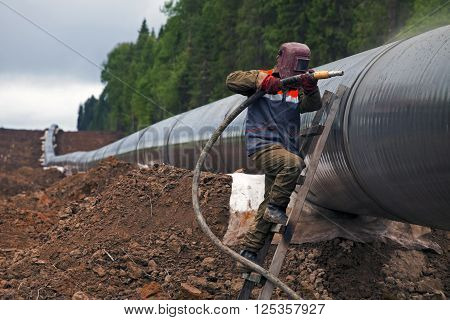 Worker using a sandblaster cleans tubing pipe before insulation