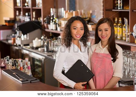 Portrait of female Vietnamese bar owner and waitress behind the counter