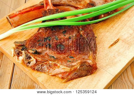 served main course: boned roasted lamb ribs served with green chives on wooden board