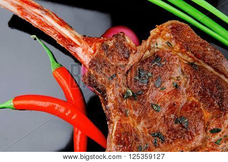 meat savory : grilled beef ribs served with green chives and raw red chili peppers over black plate