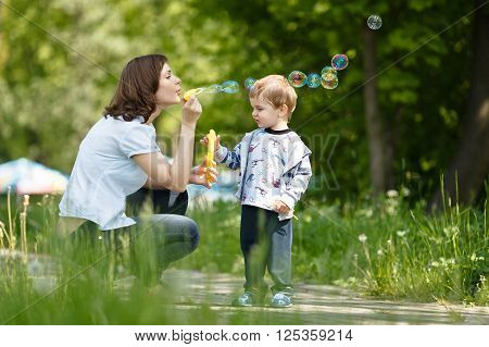 Mother with her son blowing bubbles at summer day