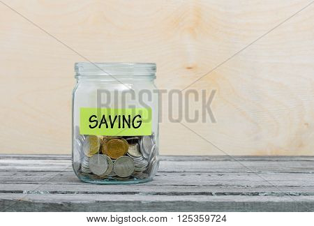 Label on a glass jar with the inscription - saving. Glass jar with coins. Financial concept on wooden background