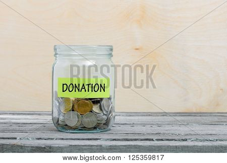 Label on a glass jar with the inscription - donation. Glass jar with coins. Financial concept on wooden background
