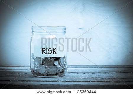 Label on a glass jar with the inscription - risk. Glass jar with coins. Financial concept on wooden background