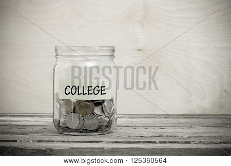 Label on a glass jar with the inscription - college. Glass jar with coins. Financial concept on wooden background