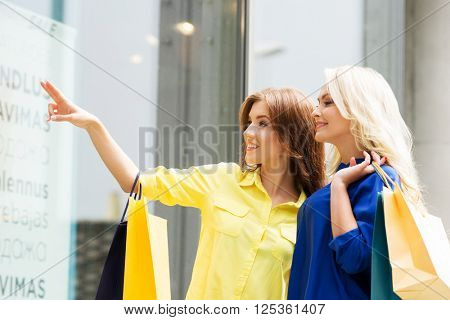 Beautiful blond and brunette shopaholic women pointing at showcase.