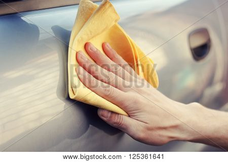 waterless car wash. Men's hand with yellow cloth cleaning car photo with toning