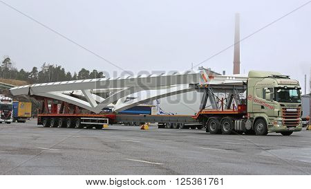 NAANTALI, FINLAND - APRIL 9, 2016: Scania R620 and long industrial object on drop deck trailer as oversize load. The length of the vehicle is 42 meters.