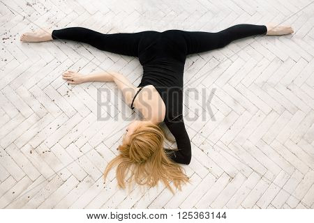 Pretty young blonde woman in black lying on the floor and doing twine