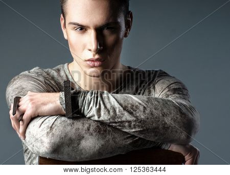 Young elegant sexy fashion handsome caucasian man sitting in the chair. Stylish portrait of a man in casual clothing in the studio which looks directly into the frame.
